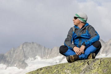Alpinist enjoys the peace and solitude in the Swiss Alps