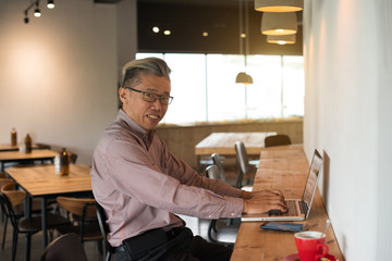 asian senior male using laptop in cafe