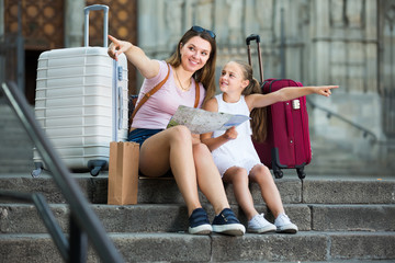 attractive young woman with daughter resting on stairs reading paper map during vacation