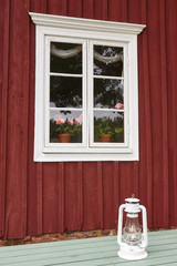Traditional red wooden farm facade with window and flowers. Finland