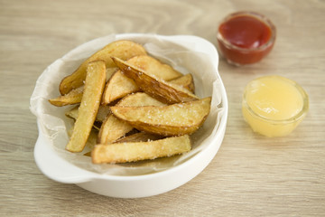 WHITE BOWL FRENCH FRIES Deep fried french fries served on a white bowl with tomato sauce and mayonnaise.