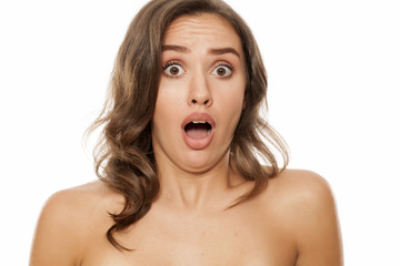 Portrait of beautiful young negativly surprised woman on white background