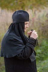 the old nun kisses his rosary with nature