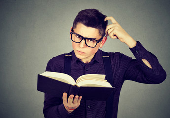 Confused man in glasses perplexed after reading a book