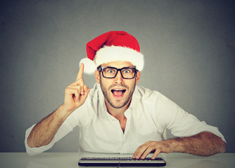 Happy christmas man in red santa claus hat buying stuff online. Holiday xmas shopping