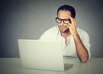 Pensive businessman wearing glasses sitting at desk working on his laptop
