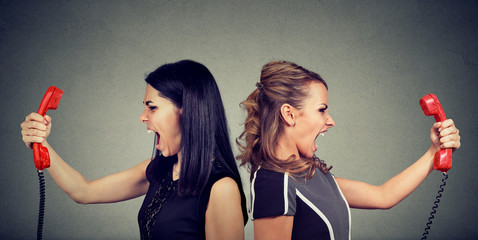 Communication concept. Two angry women screaming at each other over the phone