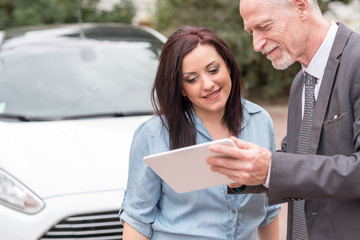 Car salesman giving informations on tablet to young woman