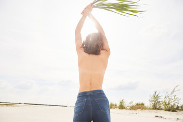 An asian girl topless walking around a beach on sand in backlight with a bunch of grass