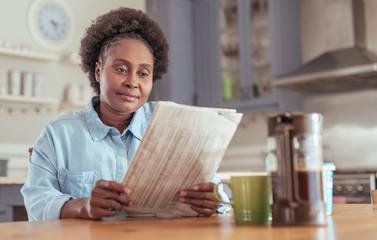 Young woman drinking coffee and reading the newspaper at home