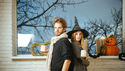 Halloween macho and girl in witch hat holding cups