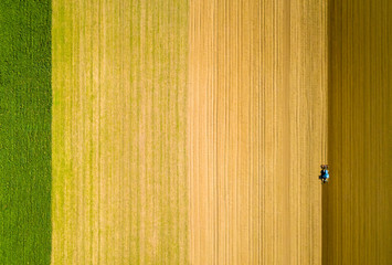 Drone view of a farmer plowing his field with his tractor