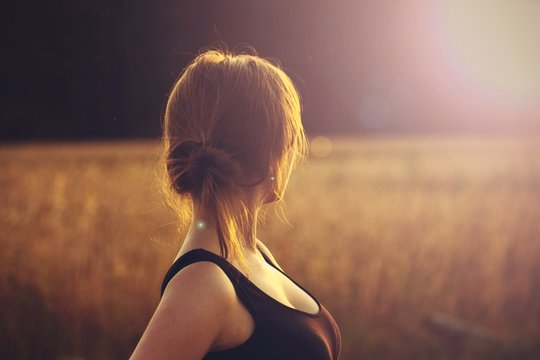 The girl from the back at sunset. The summer landscape
