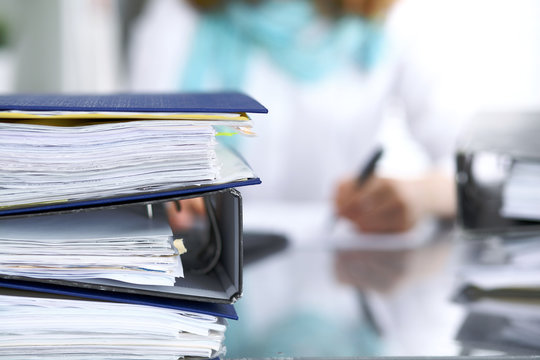 Binders with papers are waiting to be processed with businesswoman or secretary back in blur. Internal Revenue Service inspector checking financial document