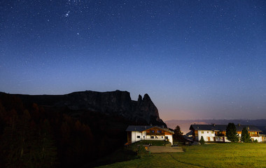 Wall Mural - Alpine village, night scene beneath the epic star sky. Location: Italy, South Tyrol, Dolomite mountains. Famous and popular all seasons resort. Autumn season.