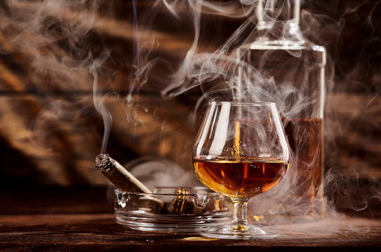 Glass of cognac or brandy with smoking cigar on wooden table.A lot of smoke