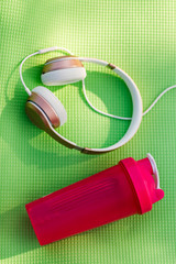 Photo of headphones, pink water bottle