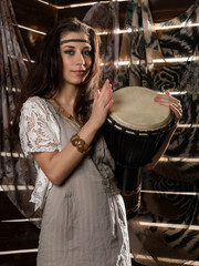 Young hippie boho woman having fun ans plays the Jamaica drum. Hippie style