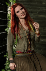 Young hippie boho redhead woman having fun on a swing. Hippie style on a wooden background