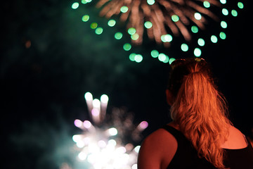 A young woman watches fireworks