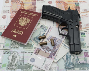 A pistol with cartridges and a passport lies on the background of money