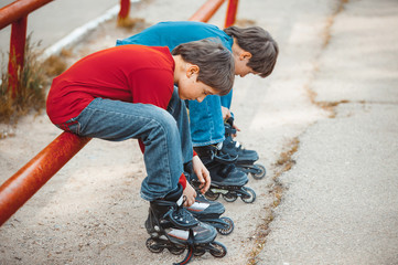 boys lace his roller skate sitting on the sidewalk