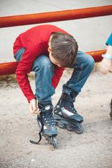 boy lace his roller skate sitting on the sidewalk