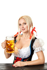 Waitress in traditional german costume holding beer glass on Oktoberfest.