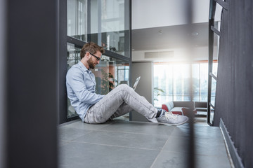 Man using laptop sitting on stairs in office