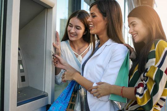 Happy young women using cash machine. Women using credit card.