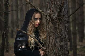 Halloween. beautiful girl in a black dress in the forest