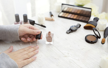 Female hands applying nail polish on table with cosmetic products at home.