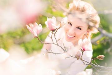 Beautiful Woman smiling among magnolia flowers