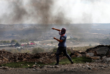 A Palestinian protester hurls stones towards Israeli troops during clashes near the Jewish settlement of Qadomem, in the West Bank village of Kofr Qadom near Nablus