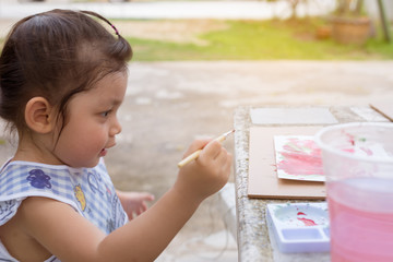 Cute Asian little girl concentrate to painting watercolor and sitting on table in garden