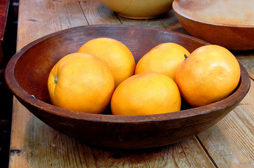 Wooden bowl with oranges