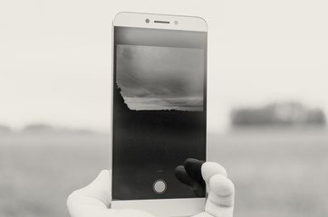 The phone's gadget in someone's hand takes a photo or video.