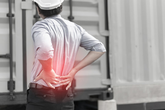 Engineer with back pain on construction site background,Highlights of the man with a waist to hip pain,Asian Business people having hip pain