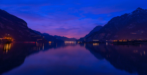 Central Switzerland, Lake Lucerne. Night landscape. Royal blue. The mountain range, the light of lanterns and lamps are reflected in the lake, long exposure