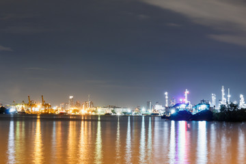 Commercial docks with light at  night with a ship and crane