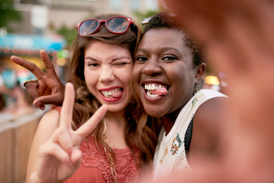 Diverse group of two girls taking selfies photos in the crowd of a summer music festival