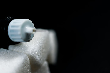 Sugar cubes on focus, insulin pen on the top, diabetes prevention conceptual image.