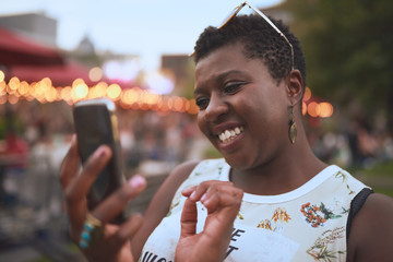 Authentic young african american woman using a mobile phone at a summer music festival
