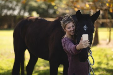 Happy woman taking selfie with horse at barn