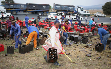 Locals loot beer after a truck lost control on a motorway outside Johannesburg,South Africa