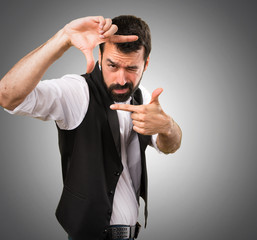 Cool man  focusing with his fingers on grey background