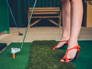 Woman in heels on golf driving range