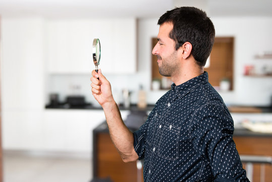 Brunette man with magnifying glass inside house