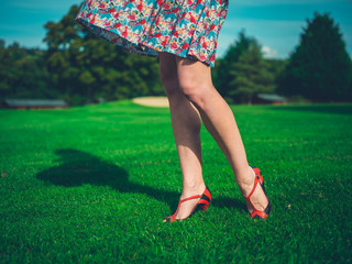 Woman standing on lawn with wind in dress