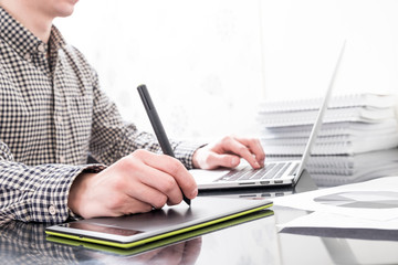 Designer working with graphics tablet and laptop in office